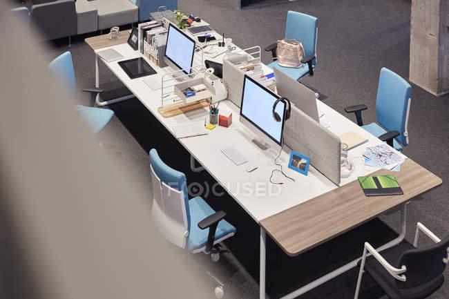 Mesa en la oficina moderna con monitores en blanco - foto de stock