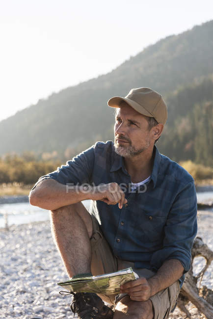 Mature man camping at riverside, sitting on tree trunk with map — Stock Photo