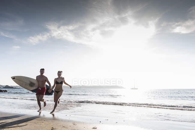 France, Brittany, happy young couple with surfboard running hand in hand in the sea — Stock Photo
