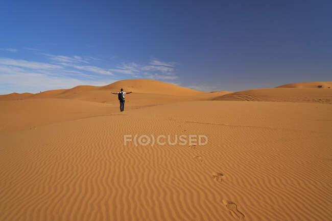 Marocco, vista posteriore dell'uomo con zaino in piedi sulle dune del deserto — Foto stock