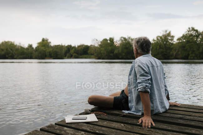 Anziani seduti sul molo in un lago — Foto stock