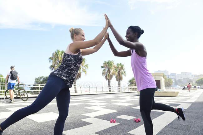 Two happy women doing fitness exercises outdoors — Stock Photo