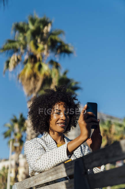 Beautiful woman sitting on a bench in the city, takig pictures with her smartphone — Stock Photo