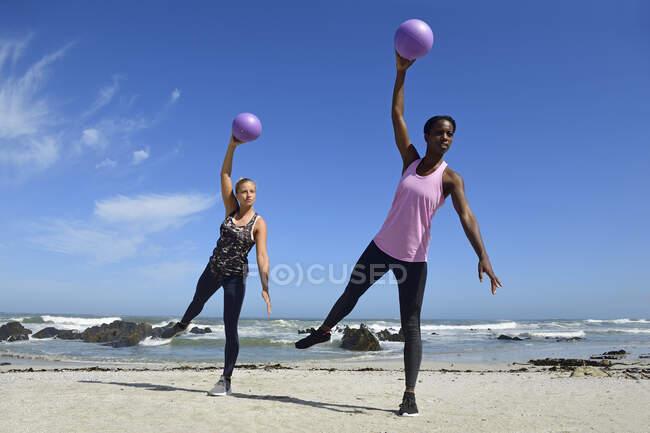 Due donne che fanno esercizi di fitness con palla sulla spiaggia — Foto stock