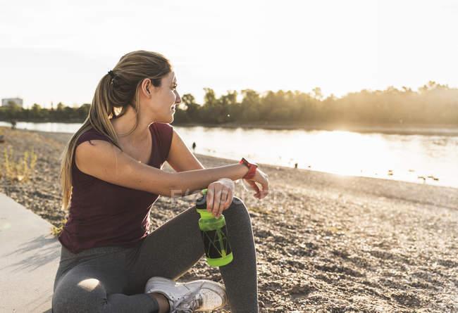 Молодая женщина отдыхает после тренировки на реке — стоковое фото