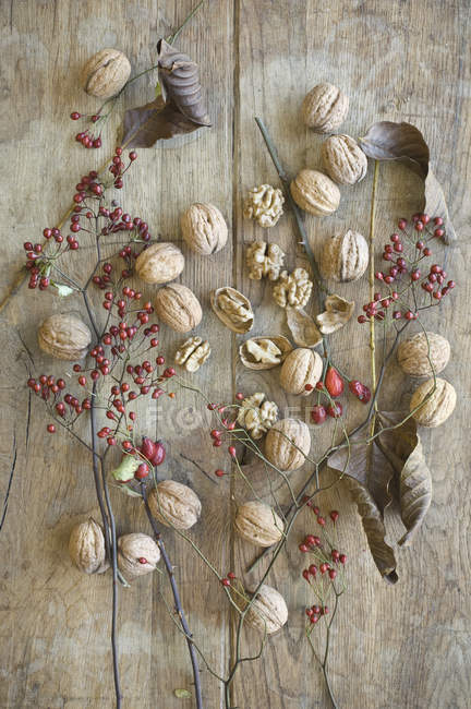 Whole and cracked organic walnuts, leaves and roseships on wood — Stock Photo