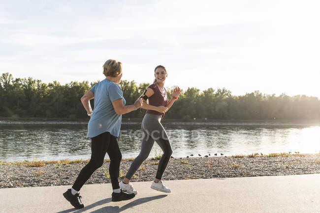 Petite-fille et grand-mère s'amusent, faisant du jogging ensemble à la rivière — Photo de stock