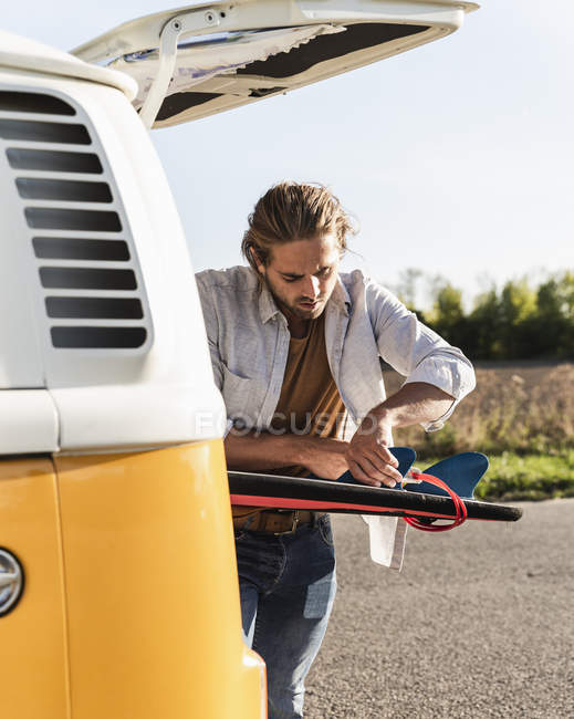 Young man on road trip with his camper, fixing surfboard on the road — Stock Photo