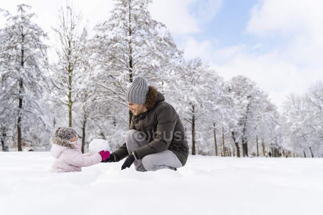 Joyeux père jouant avec sa fille dans un paysage d'hiver — Photo de stock
