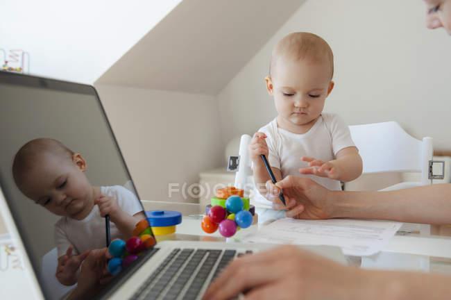 Piccola figlia che gioca e madre che usa il computer portatile a tavola a casa — Foto stock