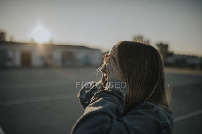 Giovane donna coprendo gli occhi al tramonto — Foto stock