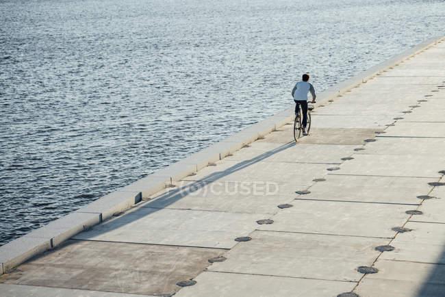 Jeune homme à vélo sur la promenade riveraine au bord de la rivière — Photo de stock