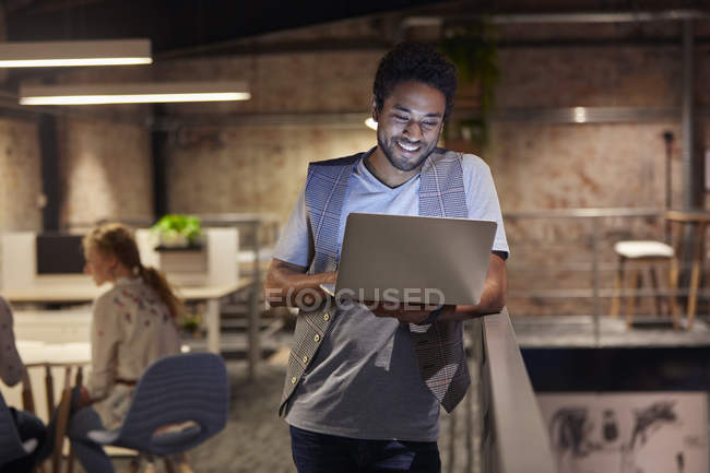 Young man working in creative start-up company, using laptop — Stock Photo
