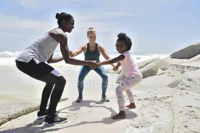 Мать с дочерью и другом занимаются фитнесом на пляже — стоковое фото