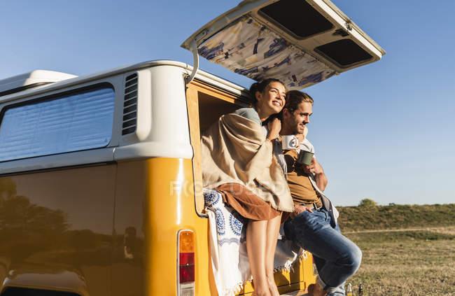 Glückliches Paar auf einem Roadtrip mit dem Wohnmobil, auf dem Bett sitzend, Kaffee trinkend — Stockfoto
