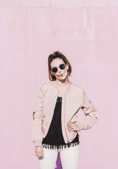 Portrait of young woman wearing sunglasses and grimacing in front of pink wall — Stock Photo