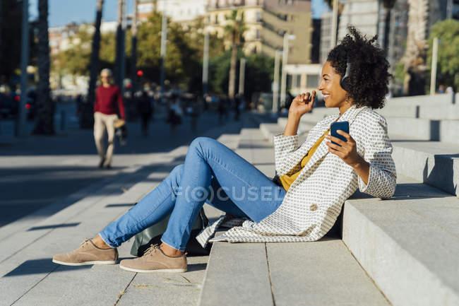 Прекрасна жінка сидить на сходах міста, користується смартфоном, слухає музику навушниками. — стокове фото
