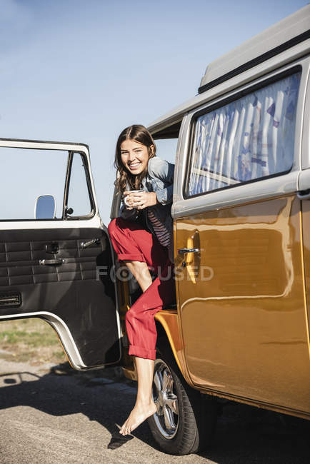 Pretty woman on a road trip with her camper, taking a break, drinking coffee — Stock Photo