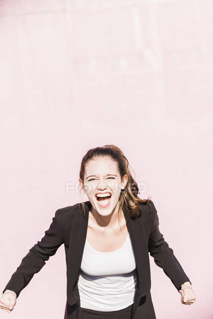 Ritratto di giovane donna urlante davanti al muro rosa — Foto stock