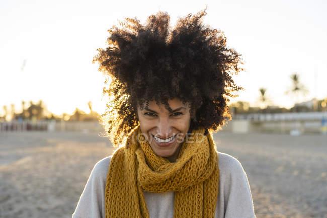 Retrato de una mujer feliz en la playa, con una bufanda amarilla - foto de stock