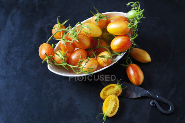 Bowl of whole and sliced cocktail tomatoes 'Artisan Blush Tiger' and an old knife on dark ground — Stock Photo