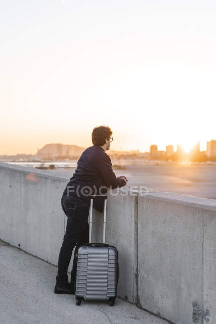 Spain, Barcelona, young businessman with rolling suitcase watching sunset — Photo de stock