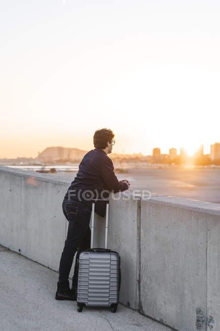 Spagna, Barcellona, giovane uomo d'affari con valigia rotolante che guarda il tramonto — Foto stock