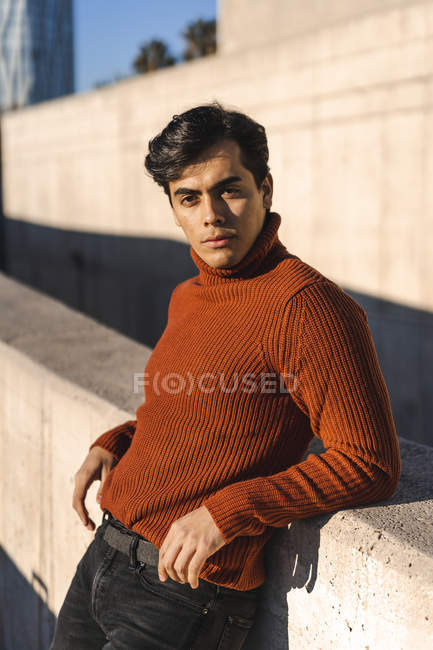 Portrait of fashionable young man wearing turtleneck pullover leaning on a wall at sunlight — Stock Photo