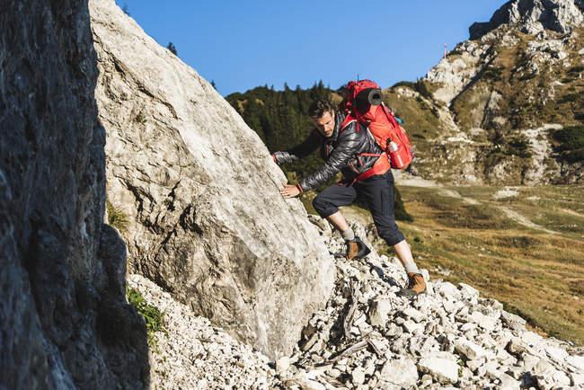 Homme randonnée en montagne en terrain rocheux — Photo de stock