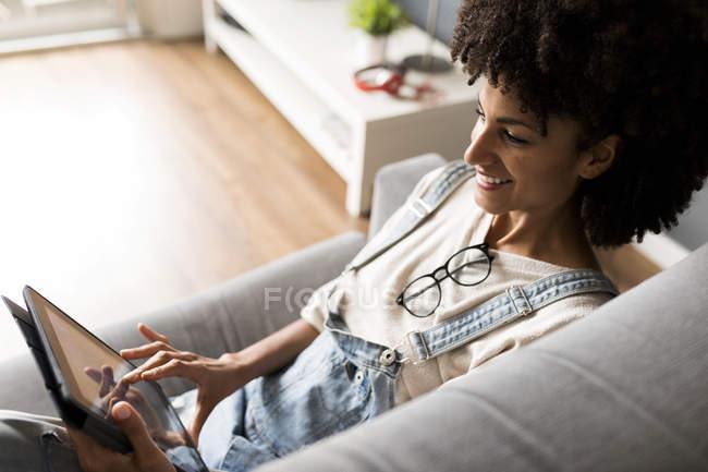 Sorridente donna sdraiata sul divano a casa utilizzando la compressa — Foto stock