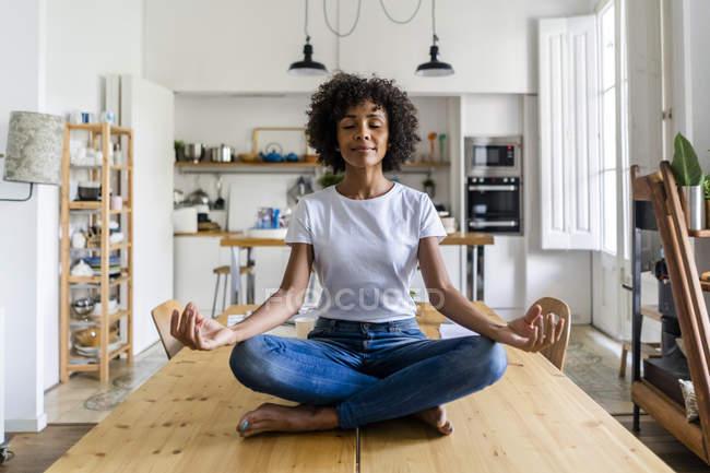 Улыбающаяся женщина с закрытыми глазами в позе йоги на столе дома — стоковое фото