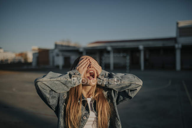 Jovem alegre cobrindo seus olhos ao ar livre — Fotografia de Stock