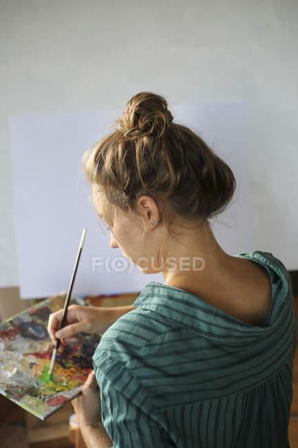Jovem com pintura de paleta em seu atelier — Fotografia de Stock