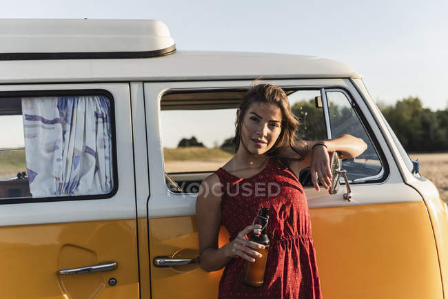 Pretty woman on a road trip with her camper, taking a break at sunset — Stock Photo