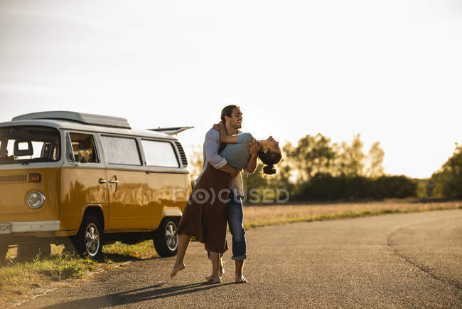 Happy couple doing a road trip with a camper, laughing and embracing on the road — Stock Photo