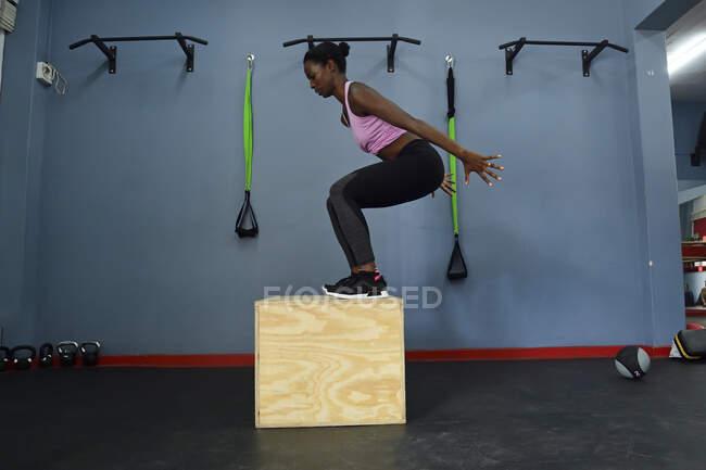 Жінка, практикуючись у спортзалі, стрибає в ящик. — стокове фото