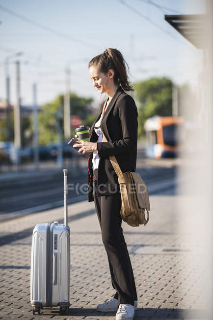 Young woman with luggage at tram station in the city using cell phone — Stock Photo