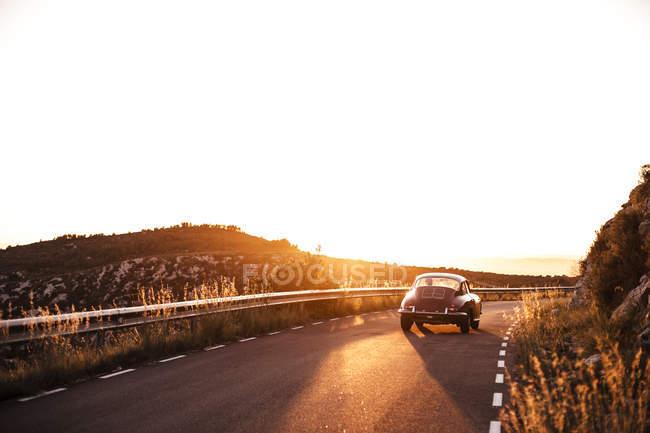 Espagne, voiture classique sur la route au coucher du soleil — Photo de stock
