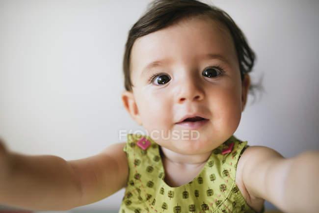Портрет дитячої дівчини, що простягнула руки на білому фоні — стокове фото