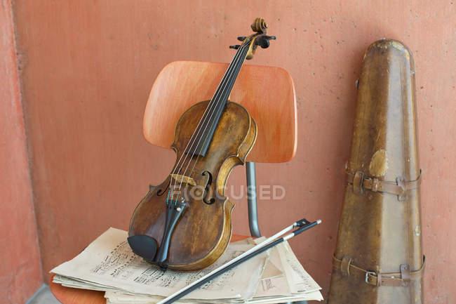 Скрипка, лук и ноты на деревянном стуле со скрипкой на заднем плане — стоковое фото