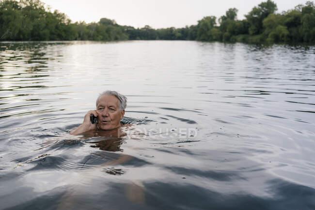 Пенсионер разговаривает по мобильному телефону в озере — стоковое фото