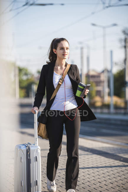 Young woman with luggage in the city on the move — Stock Photo
