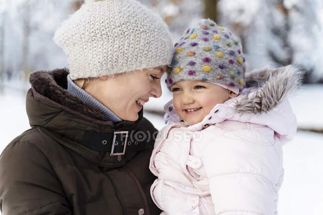 Щаслива любляча мати, яка носить дочку взимку. — стокове фото