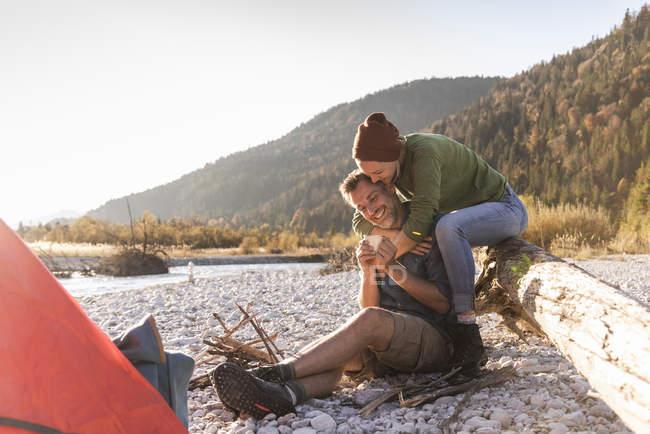 Campant de couples mûrs au bord de la rivière dans la lumière de soirée — Photo de stock
