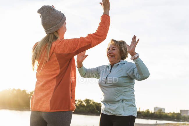 Grandmother and granddaughter high-fiving after training at the river — Stock Photo