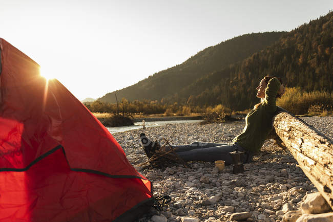 Mature woman camping at riverside in the evening light — Stock Photo