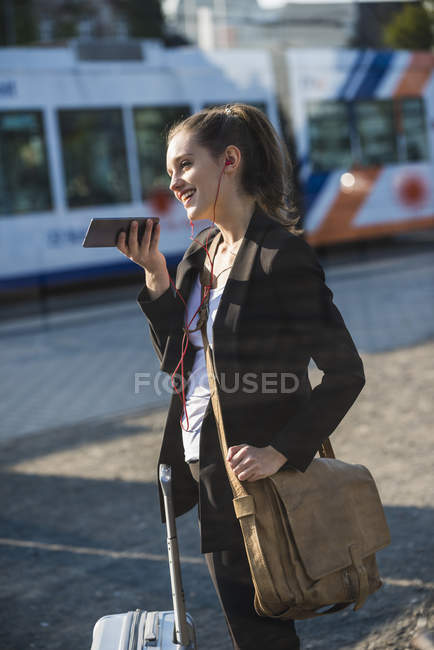 Smiling young woman with luggage at tram station in the city using cell phone — Stock Photo
