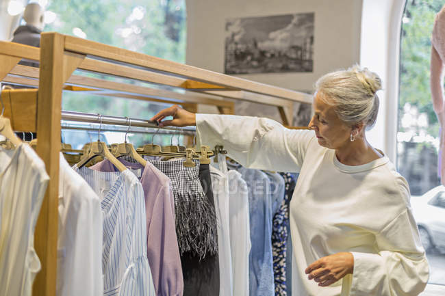 Senior woman shopping for clothes in a boutique — Stock Photo