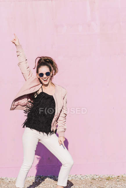 Happy young woman gesturing in front of pink wall — Stock Photo