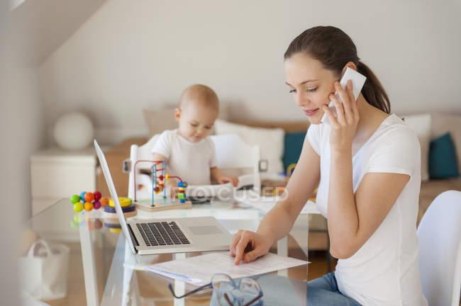 Mère travaillant et petite fille jouant à table à la maison — Photo de stock